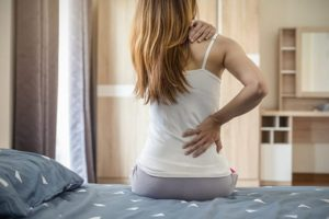 Woman suffering from back ache on the bed,